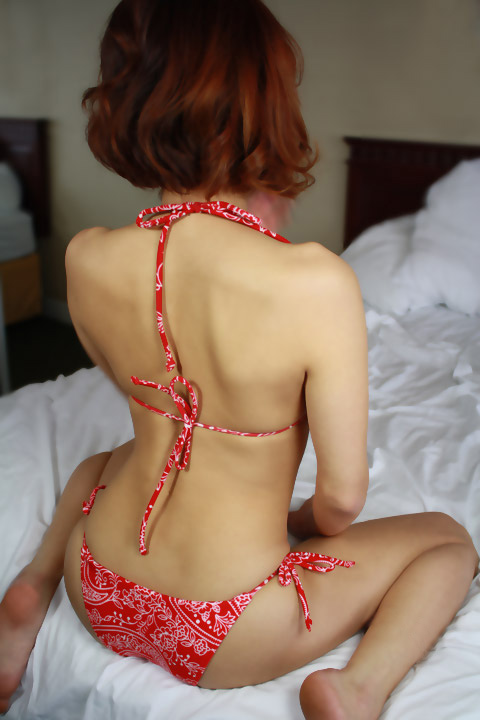 toronto escort in floral dress sitting on bed